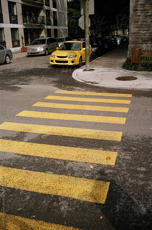 A yellow car matches the crosswalk by Erik Naumann for Stocksy United