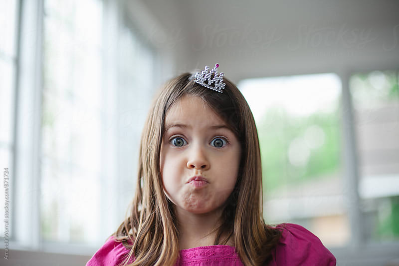 Young girl wearing a princess crown makes a silly face by Amanda Worrall for Stocksy United