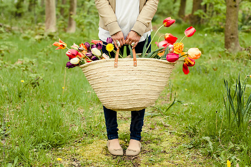 Body shot of woman holding a straw basket with flowers by Cindy Prins for Stocksy United