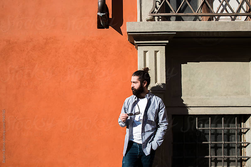 Man in front of an outdoors orange wall with window by Beatrix Boros for Stocksy United
