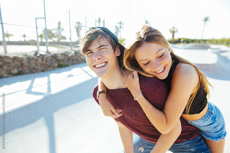 Smiling teenage couple having fun on a sunny summer day. by BONNINSTUDIO for Stocksy United