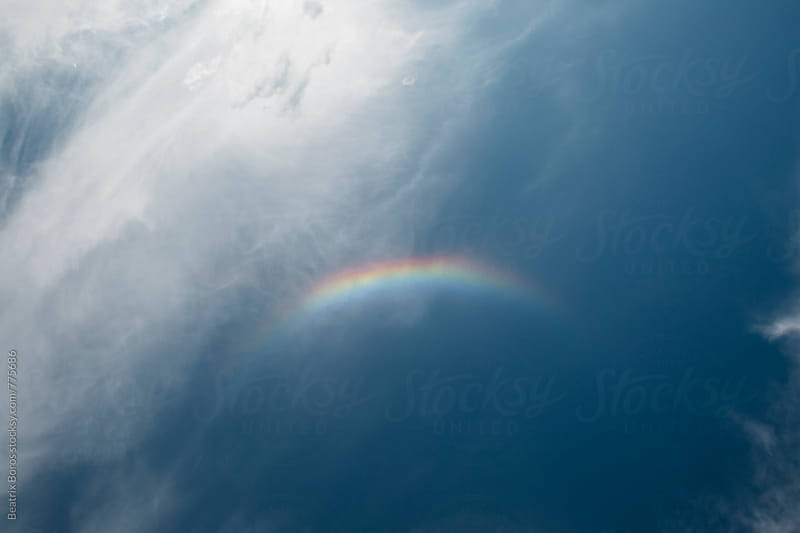 Piece of rainbow on a cloudy sky by Beatrix Boros for Stocksy United