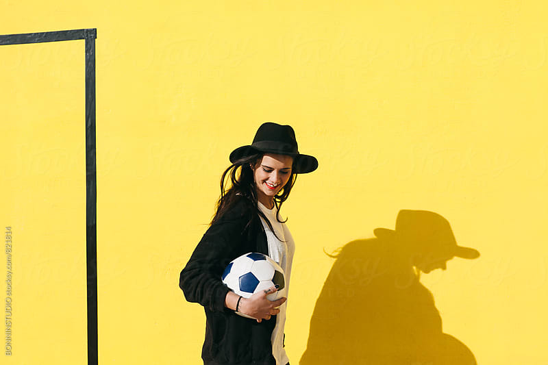 Smiling alternative woman holding a soccer ball in front of a yellow wall. by BONNINSTUDIO for Stocksy United