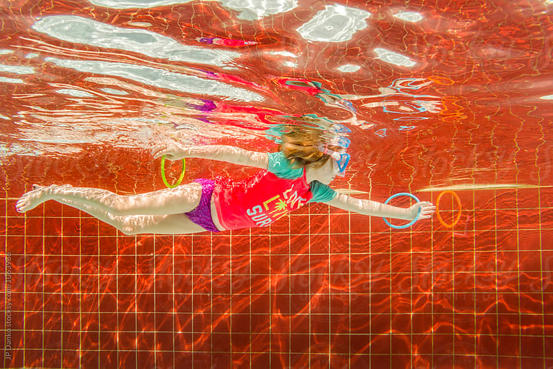 Little Girl Swimming After Rings Underwater In All Inclusive Luxury Resort Pool on Caribbean Vacation by JP Danko for Stocksy United