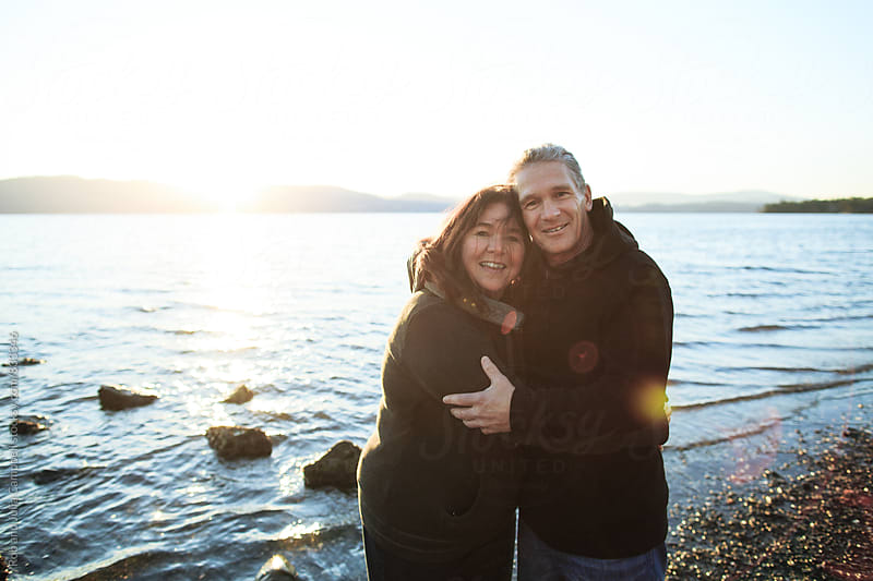 Happy, mature couple enjoying each other at the beach at sunset - smiling at camera by Rob and Julia Campbell for Stocksy United