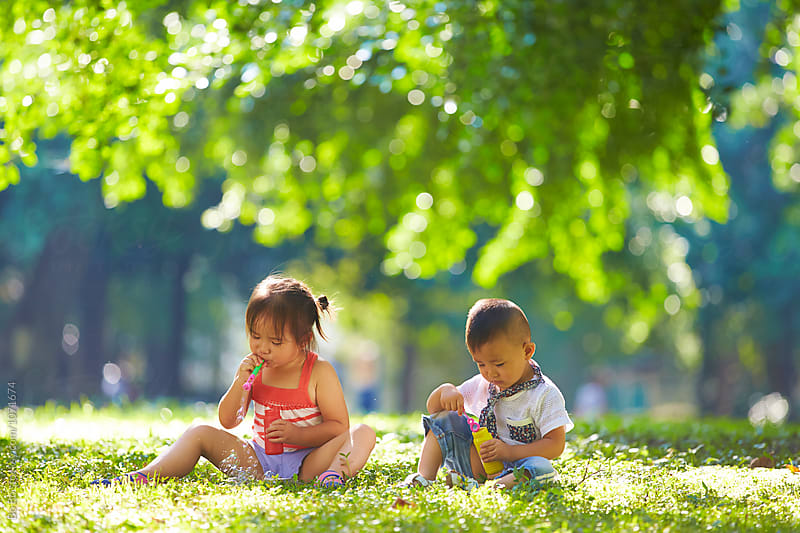 adorable kids playing with bubble outdoor in the sunny park by Bo Bo for Stocksy United