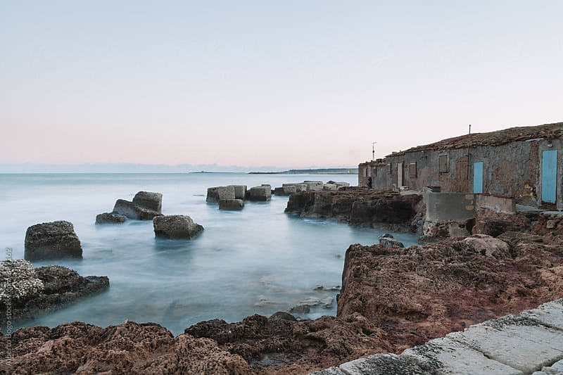 Abandoned building on rocky coastline by Alberto Bogo for Stocksy United