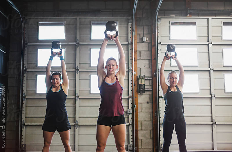Group of  friends lifting kettlebells together by Rob and Julia Campbell for Stocksy United