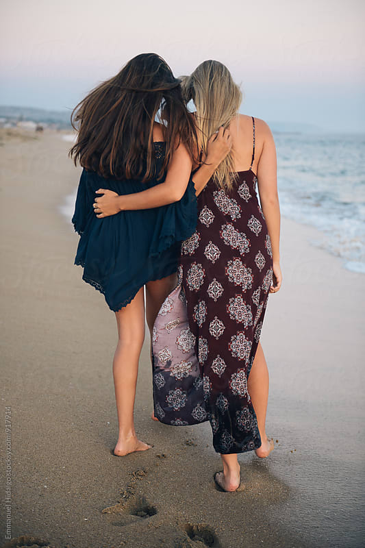 Girlfriends walking along shoreline together by Emmanuel Hidalgo for Stocksy United