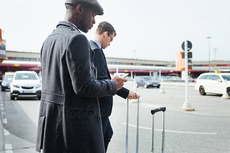 Two Business Travelers Using Smartphones as They Wait For Taxi by VISUALSPECTRUM for Stocksy United