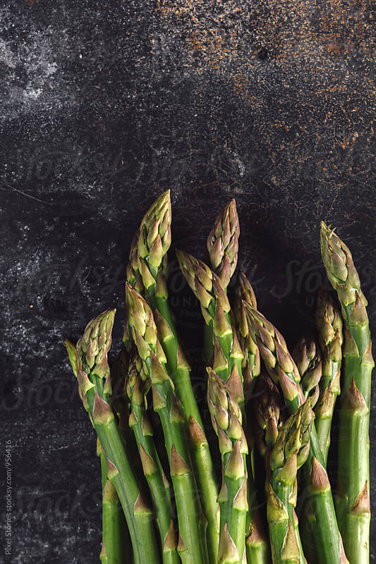 Raw asparagus on metal surface by Pixel Stories for Stocksy United