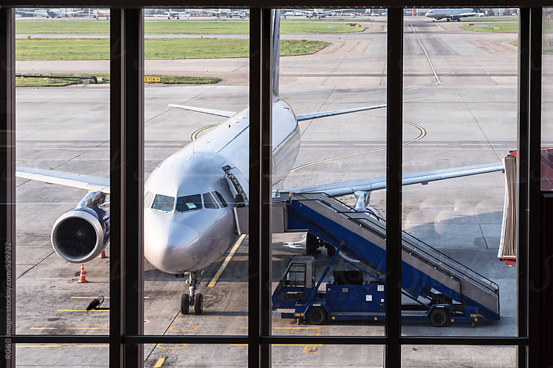 Airplane by the window in the airport  by RG&B Images for Stocksy United