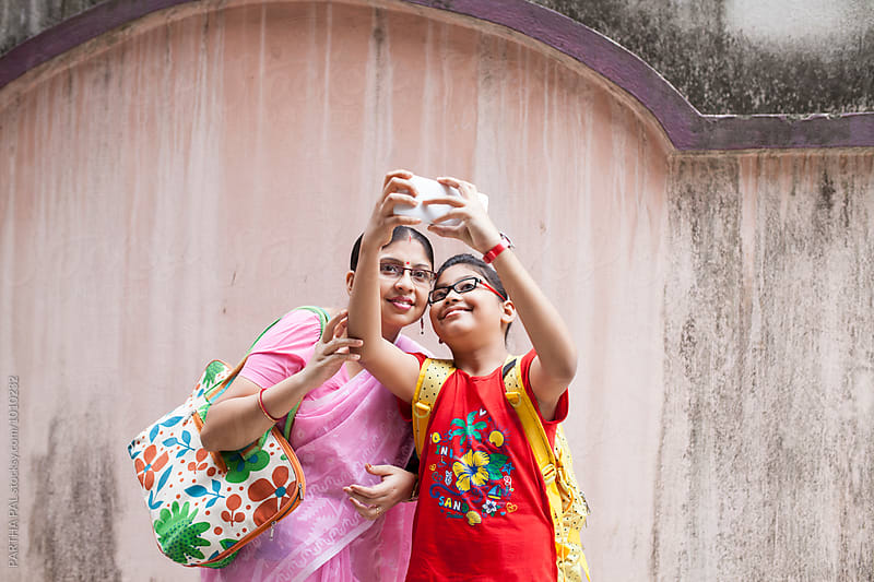 Mother and daughter capturing selfie with smartphone by PARTHA PAL for Stocksy United