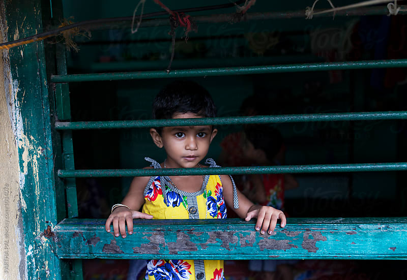 A liitle girl looking through a window by PARTHA PAL for Stocksy United