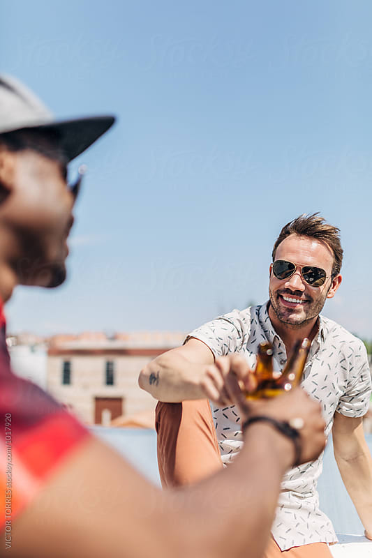 Smiling Friends Cheering with Beer on a Rooftop by Victor Torres for Stocksy United