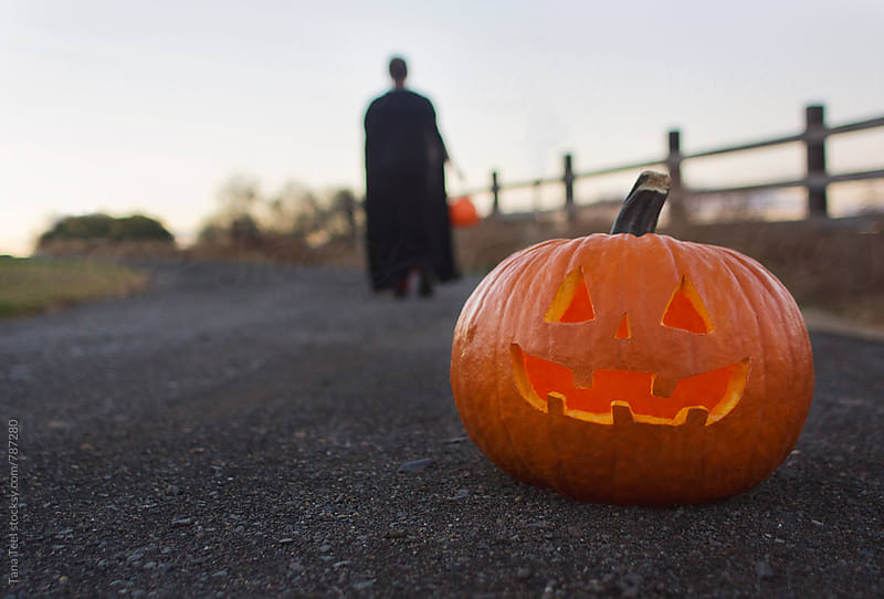 lit jack o'lantern in road with trick-or-treater in background by Tana Teel for Stocksy United