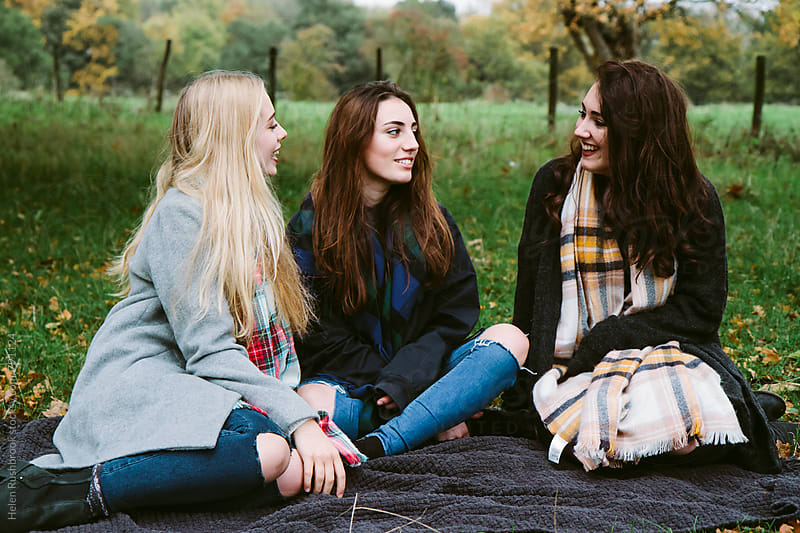 Teenage girls hanging out in the countryside. by Helen Rushbrook for Stocksy United