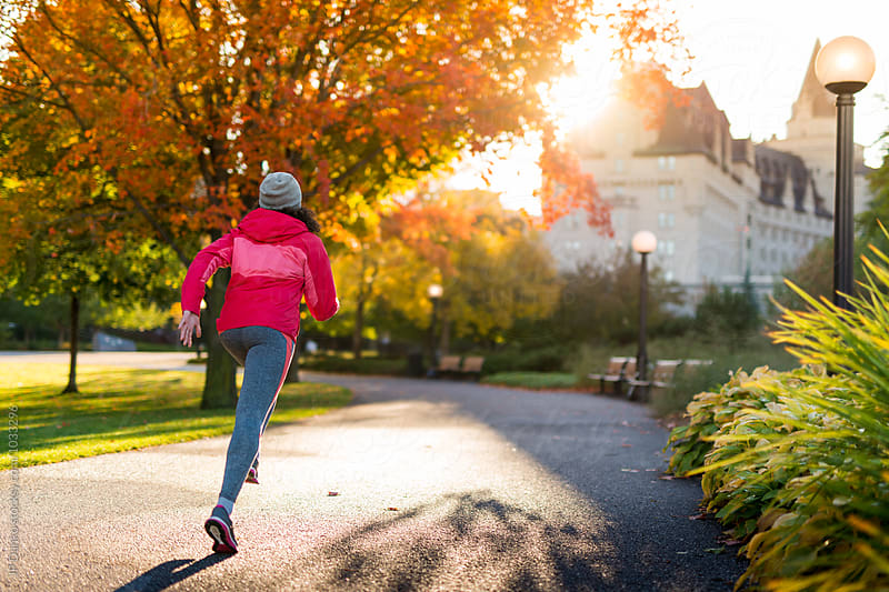 Young Woman Jogging In Ottawa Park Near Parliament Hill in Autumn by JP Danko for Stocksy United