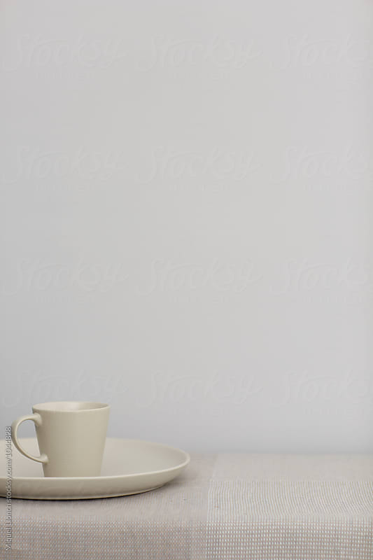 Plate and cup on a table with plain background by Miquel Llonch for Stocksy United
