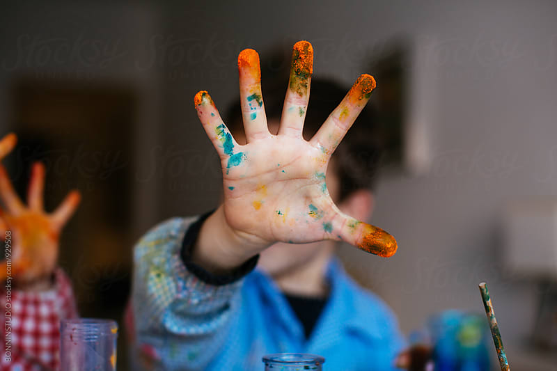 Little boy showing his colorful dirty hand. by BONNINSTUDIO for Stocksy United