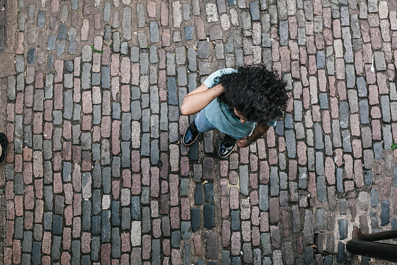 Muslim Man Walking Through a Cobblestone Street seeing from Above by VICTOR TORRES for Stocksy United