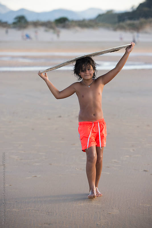 Boy holding a Surf slide board at the beach by Marta Muñoz-Calero Calderon for Stocksy United