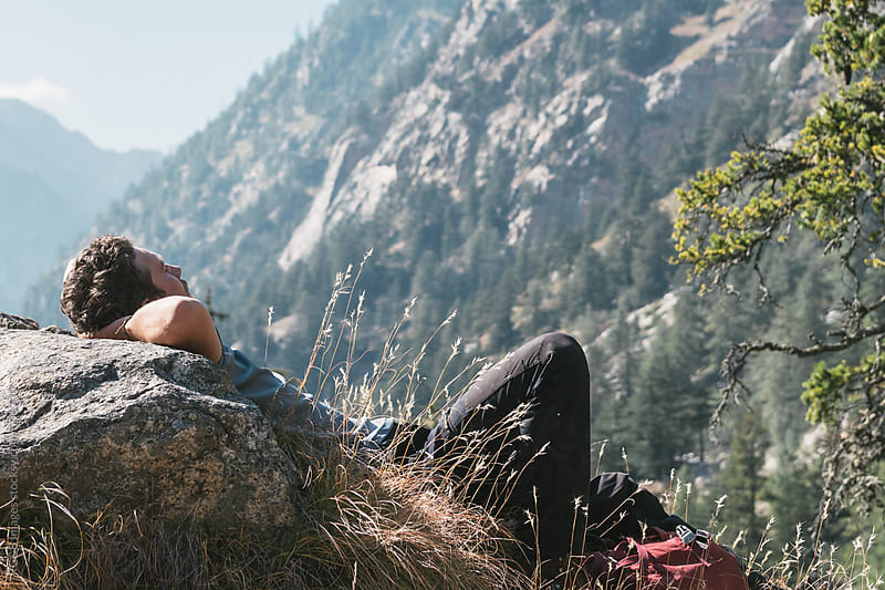 hiker taking a break resting on a rock  by RG&B Images for Stocksy United