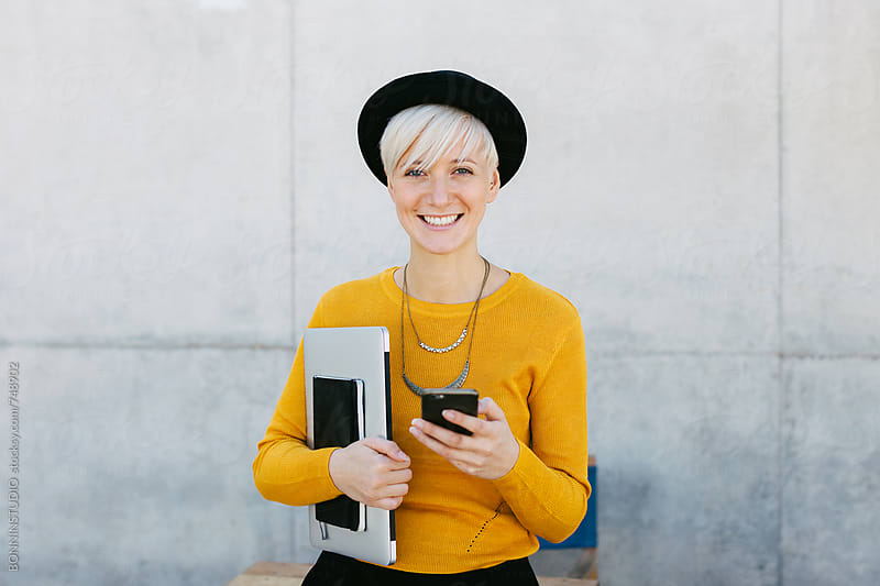 Smiling woman holding her phone on the street. by BONNINSTUDIO for Stocksy United