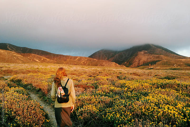 Woman Walking on Wildflower Trail by Kevin Russ for Stocksy United