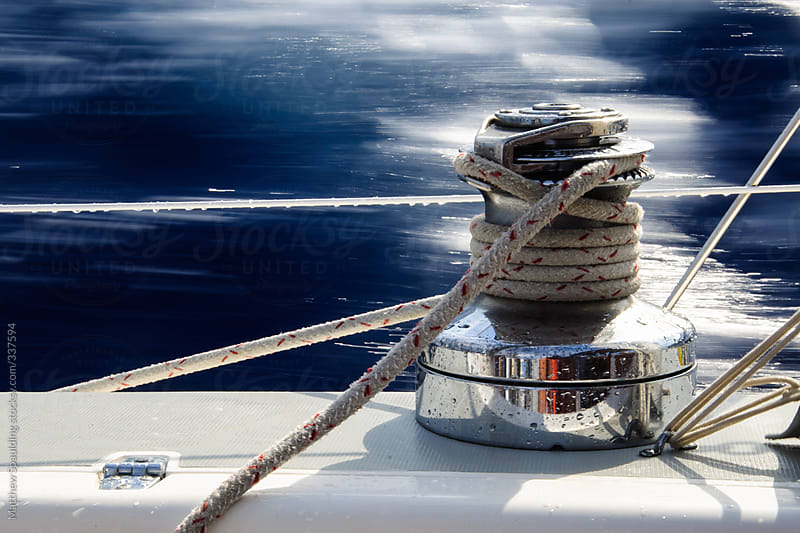Sailing winch with line on leeward side of sailboat with blue water motion blur by Matthew Spaulding for Stocksy United