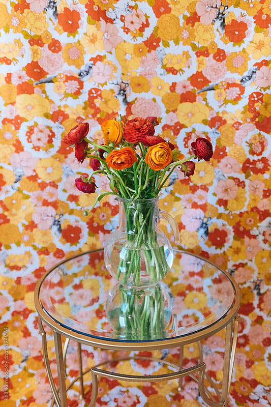 Bouquet of red and orange flowers on mirrored table by Kelli Seeger Kim for Stocksy United