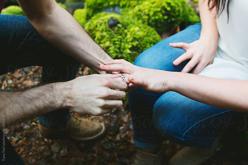 man puts ring on woman's finger by Tana Teel for Stocksy United