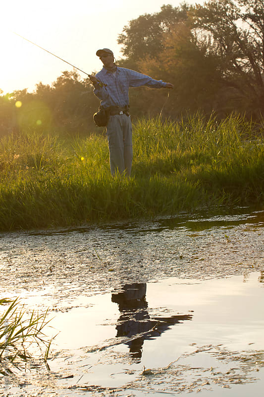 A reflection of a young man fly fishing along the river by Tana Teel for Stocksy United