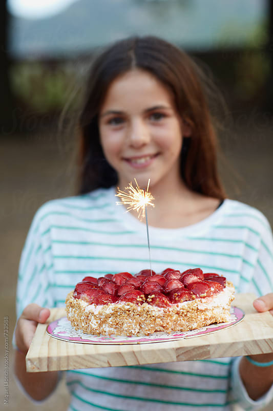 Young beautiful girl holding a birthday cake with sparckles by Miquel Llonch for Stocksy United