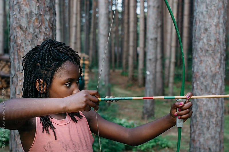 Black girl with bow and arrow aiming at target by Gabriel (Gabi) Bucataru for Stocksy United