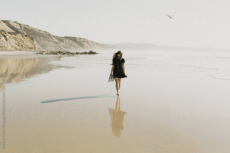 Woman walking on beach by Isaiah & Taylor Photography for Stocksy United