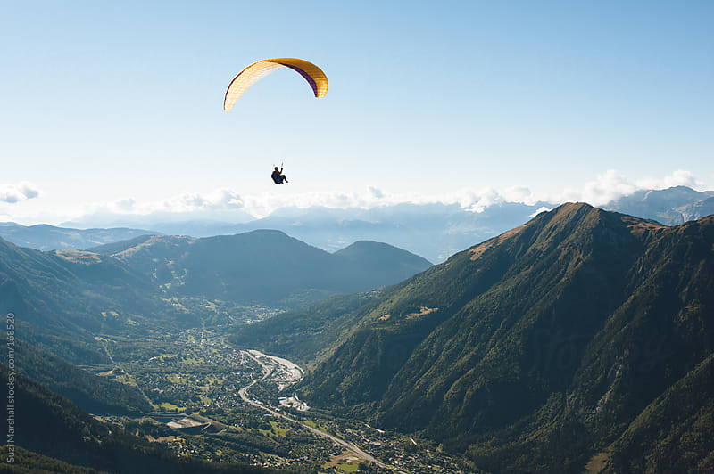 Man paragliding over mountains by Suzi Marshall for Stocksy United