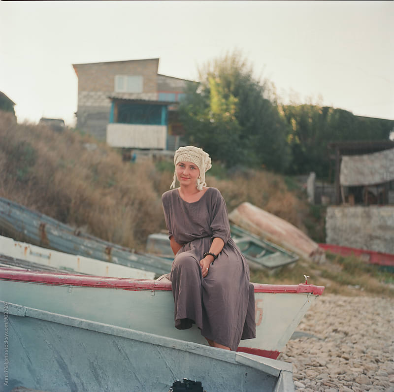 A film portrait of young beautiful woman iseating in the boat by Anna Malgina for Stocksy United