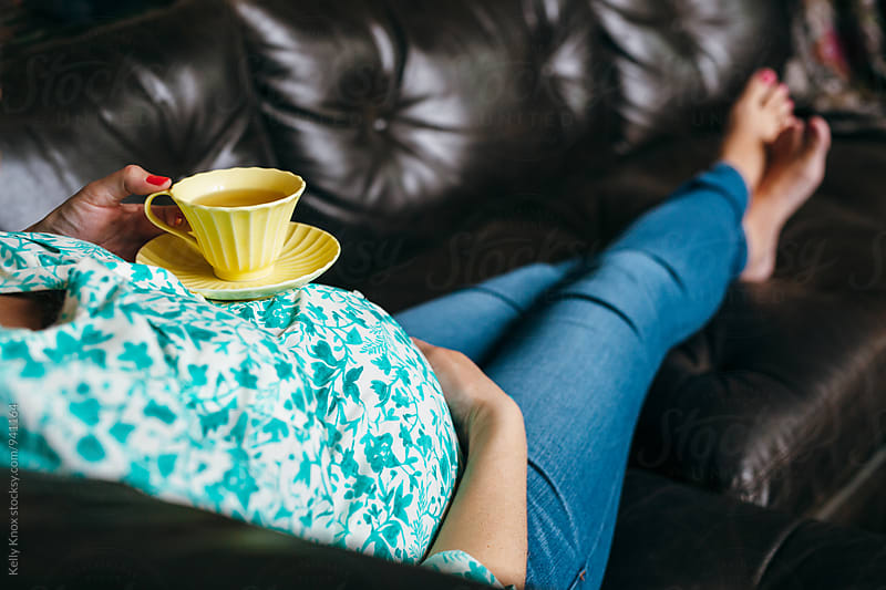 pregnant woman relaxes with a cup of tea and her feet up by Kelly Knox for Stocksy United