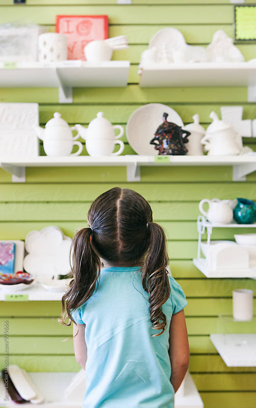 Little Girl Deciding Which Ceramic Item To Paint by Sean Locke for Stocksy United