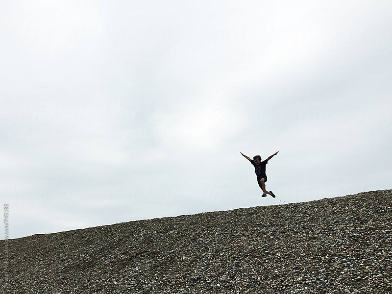 Boy jumping down a beach in Suffolk by Kirstin Mckee for Stocksy United