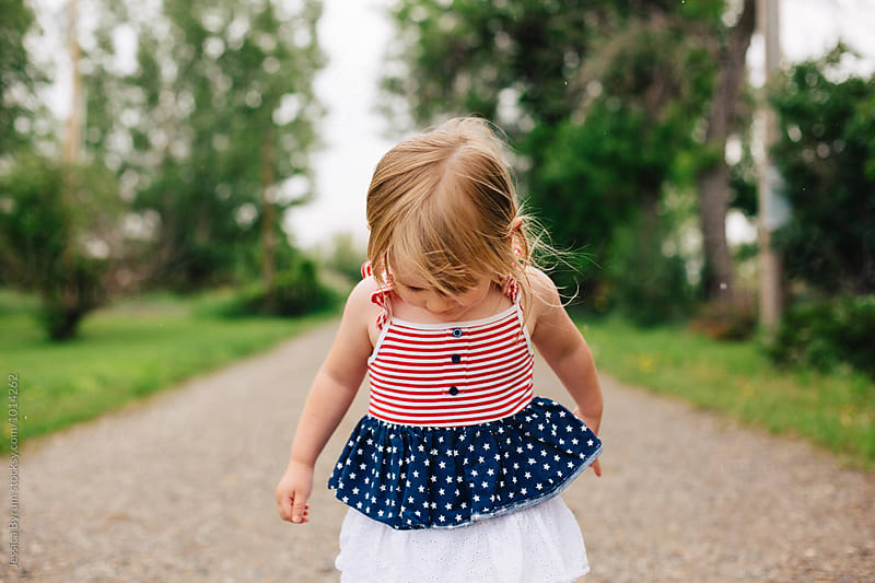 Cute girl in an American flag dress standing outside in the rain. by Jessica Byrum for Stocksy United