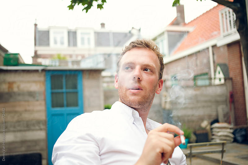 Well dressed man exhales cigarette smoke during a coffee break by Denni Van Huis for Stocksy United
