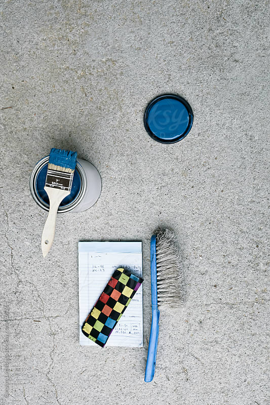 A can of blue paint on the concrete - painter's supplies by Carolyn Lagattuta for Stocksy United