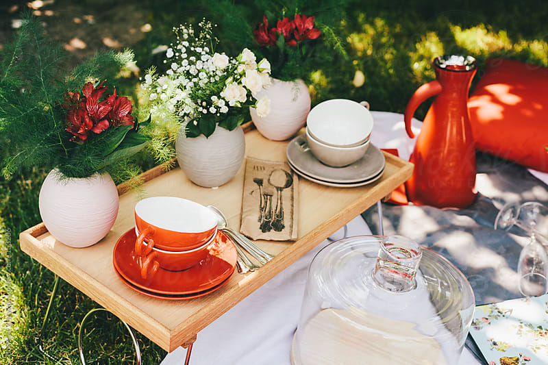 Red and gray cups on wooden tray out in the garden decorated with a lot of flowers. by Borislav Zhuykov for Stocksy United
