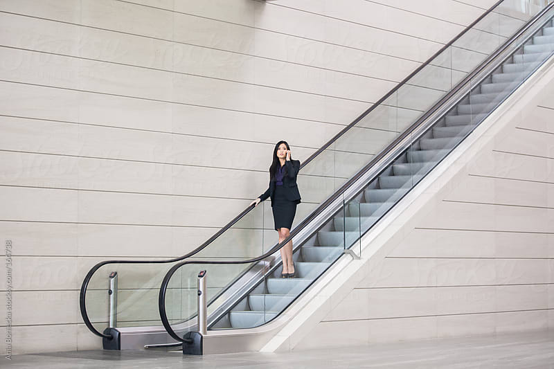 Asian businesswoman talking on her cell phone while going down on an escalator by Ania Boniecka for Stocksy United