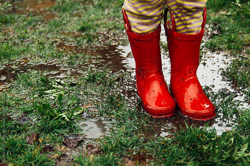 Child's feet in red rain boots on muddy grass by Gabriel (Gabi) Bucataru for Stocksy United