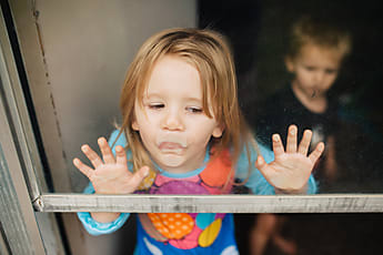 Toddler Girl Licking And Putting Her Face Against A Glass