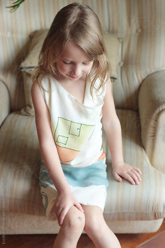 Portrait of a shy little girl with cut on her knee by Branislava Živić for Stocksy United