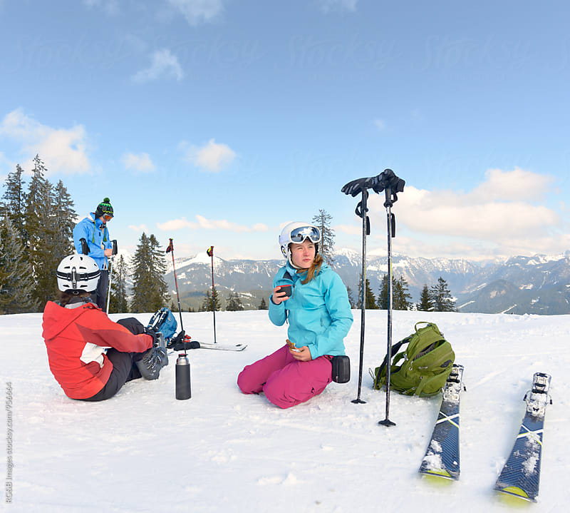 Friends having a snack on the ski slope by RG&B Images for Stocksy United